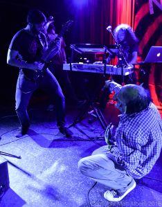 "Nekrogoblikon [clockwise]: Alex ""Goldberg "" Alereza (guitar, backing vocals), Tim Lyakhovetskiy (vocals, keyboards), Aaron ""Raptor"" Minich (keyboards), John Goblikon (mascot) - photo copyright Matt Albers (2016)"